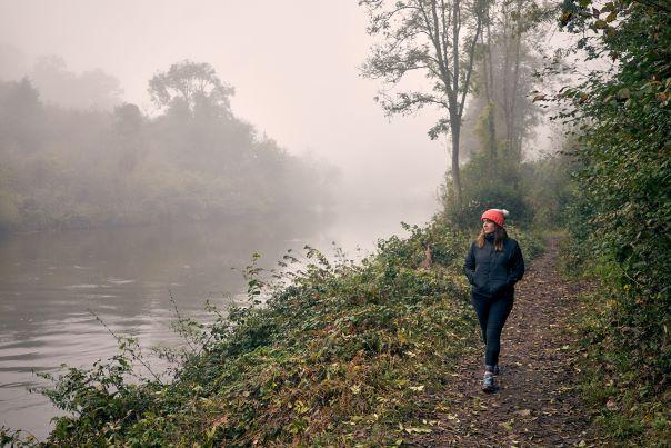 Woman walking next to river