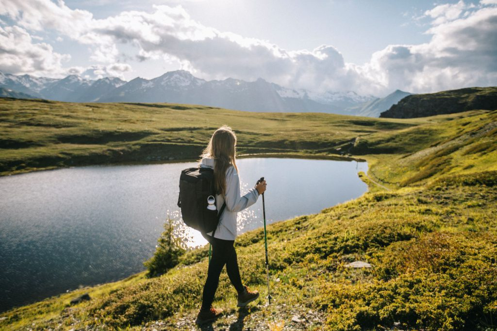 women with walking sticks by lake