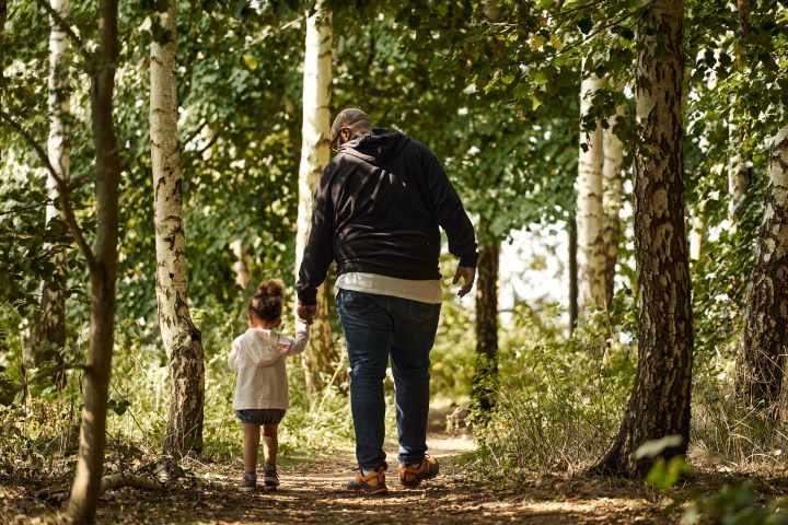 man and girl walking in the forest