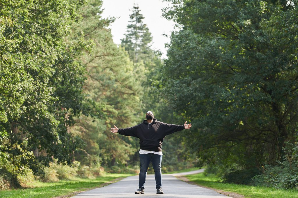 Man standing in the middle of a road with trees around him