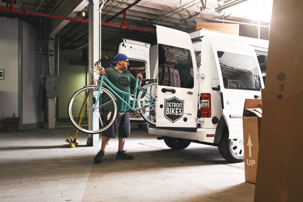 man putting bike in van