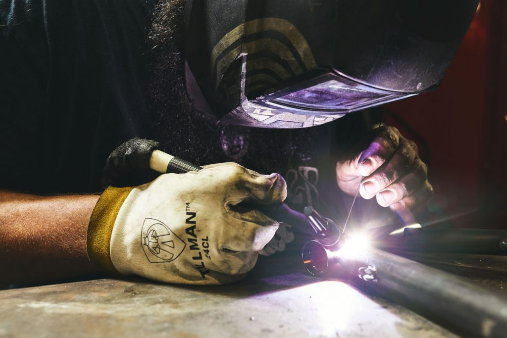 man welding metal for bike