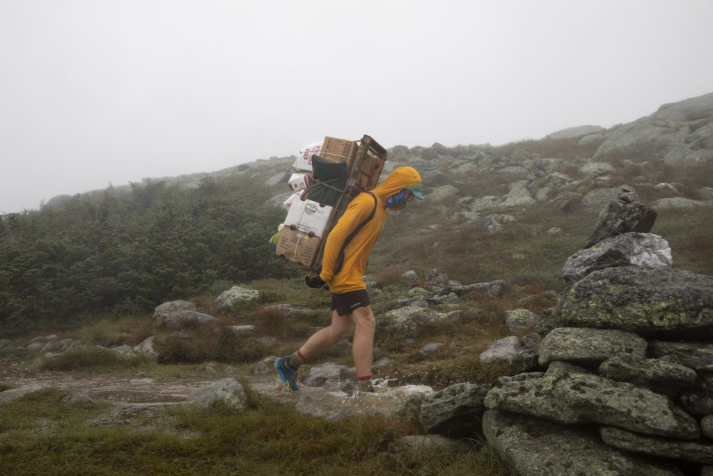man hiking through mountains with food packed on his back
