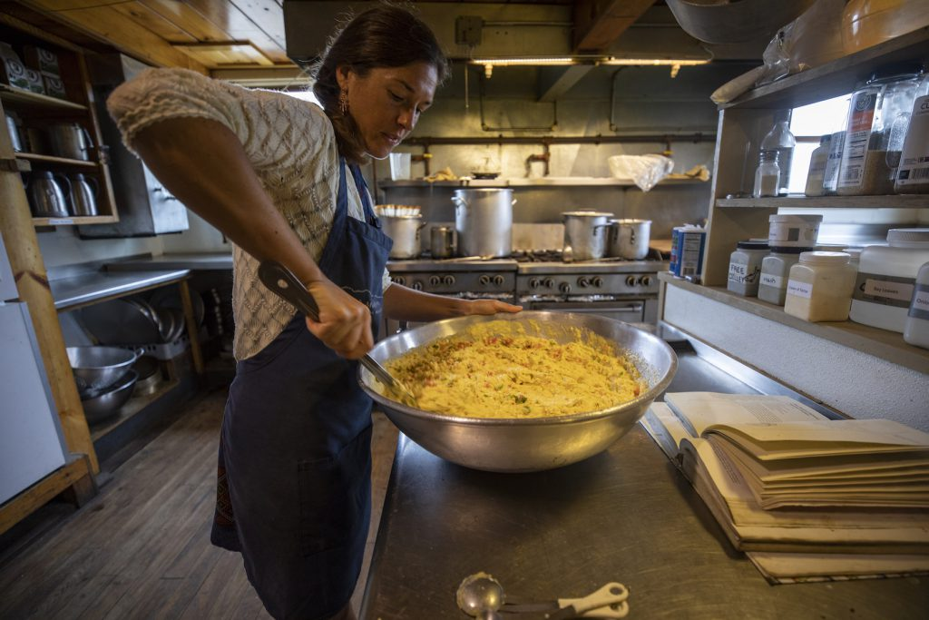 woman cooking a meal for 90 hikers in the kitchen