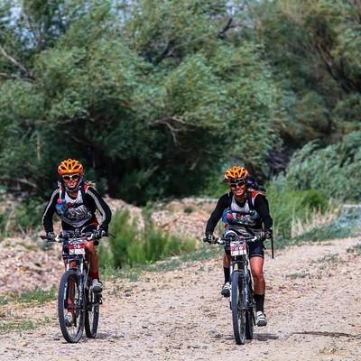 two girls riding a bike down a trail