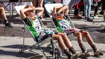 two sisters resting in a chair after they've finished a race
