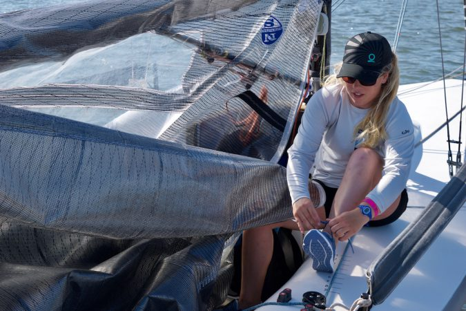 A young sailor from the War Canoe crew laces up in Sperry 7 SEAS Sport performance boat shoe before setting sail in the Melges 24 races.